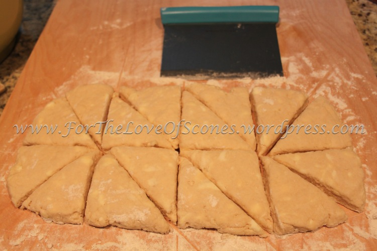 Give the dough a couple of kneads to bring it together, then flatten the dough with your hands into a log about two scone lengths in height and four scone widths in length. Divide into four rectangles, then cut each rectangle into two equal sized squares, then cut each square into two triangles, as shown.