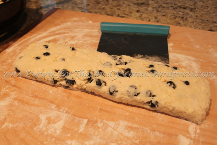 Turn the dough out onto a well-floured countertop and give a few gentle kneads to incorporate any remaining crumbs. Flatten out into a log about 1/2-inch high and one scone length in width.